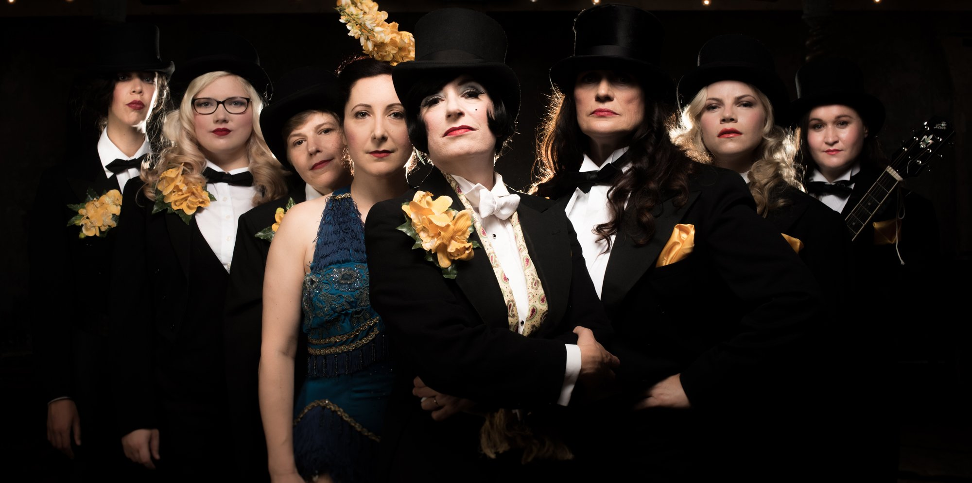 A group of women in top hats and tails. There is also a woman in a blue vintage showgirl's outfit with a yellow feather in her hair
