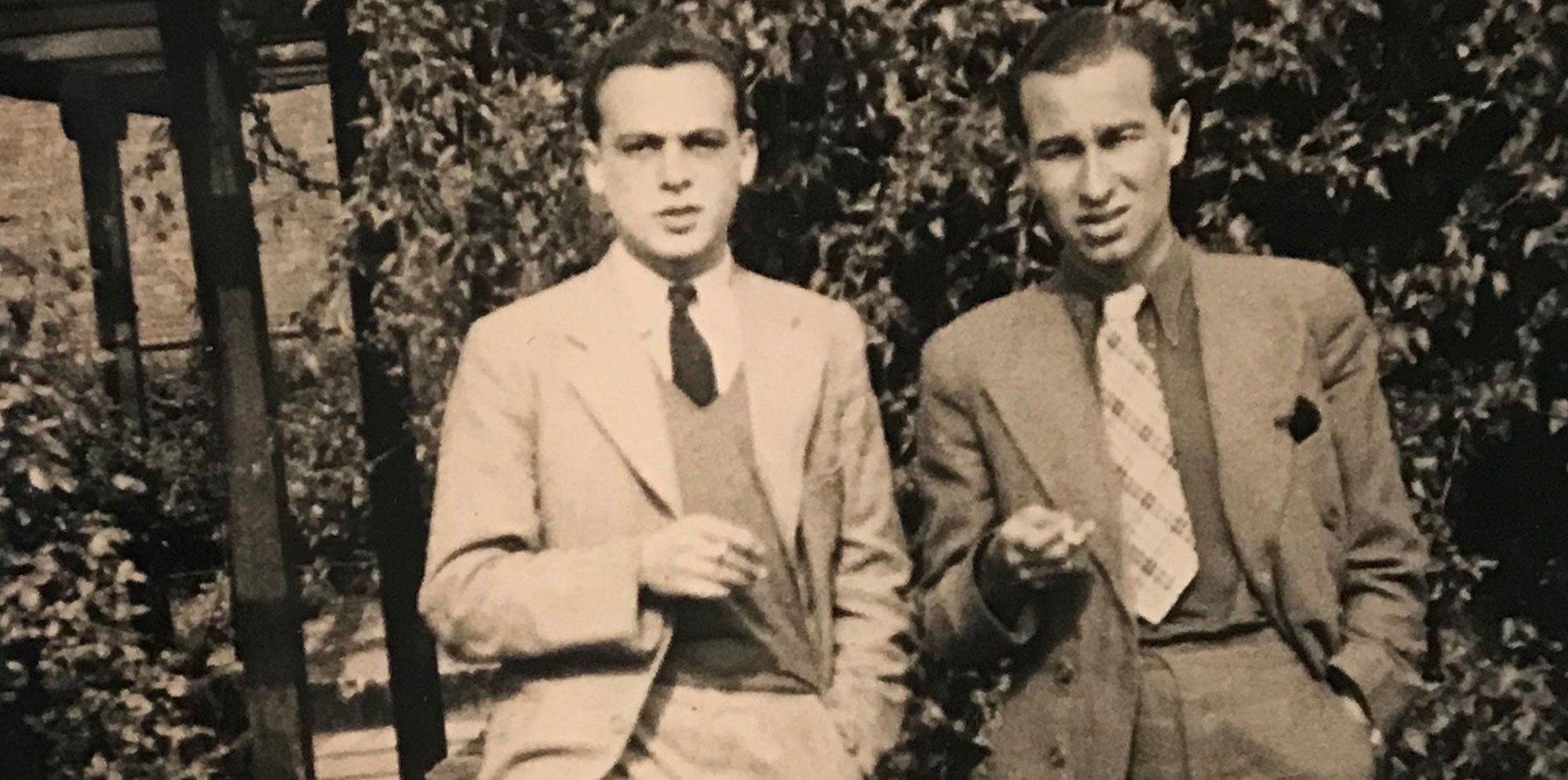 An old sepia image of two men standing in garden, holding cigarettes