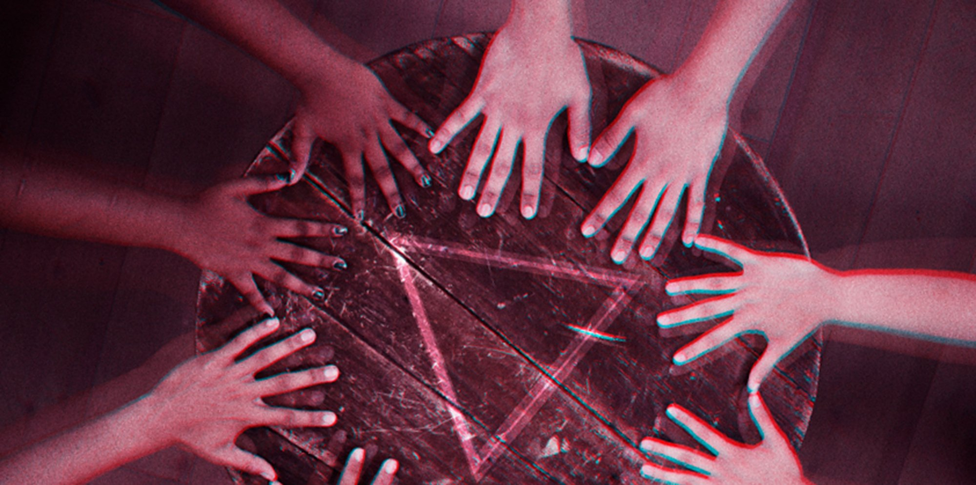 pictured from above, 4 peoples hands are placed around the edge of a round table with their little fingers touching, as if they're doing a seance. The colours in the image are strange, as if it has been badly developed.