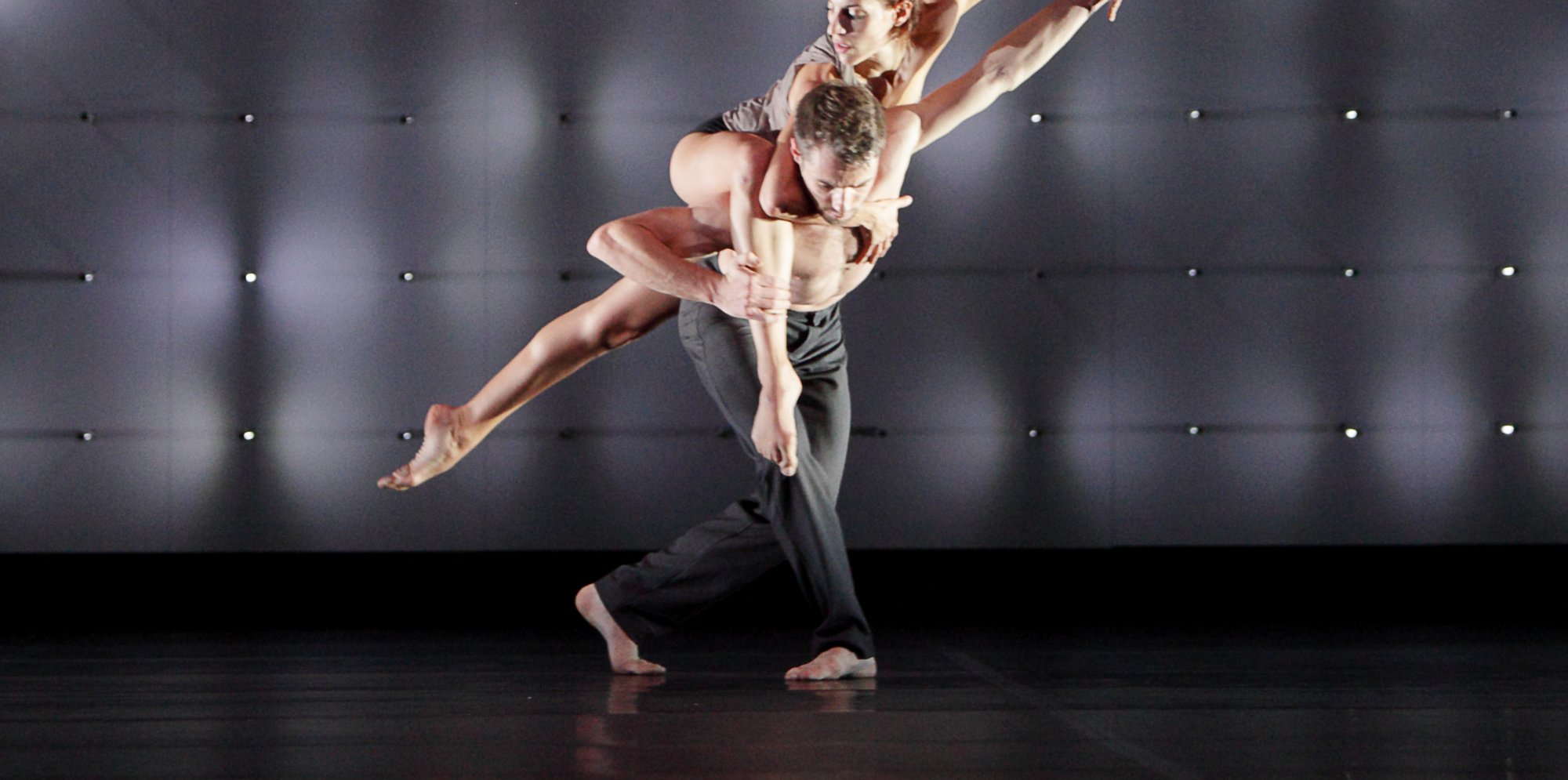 a man and a woman are dancing. she is lying across his back