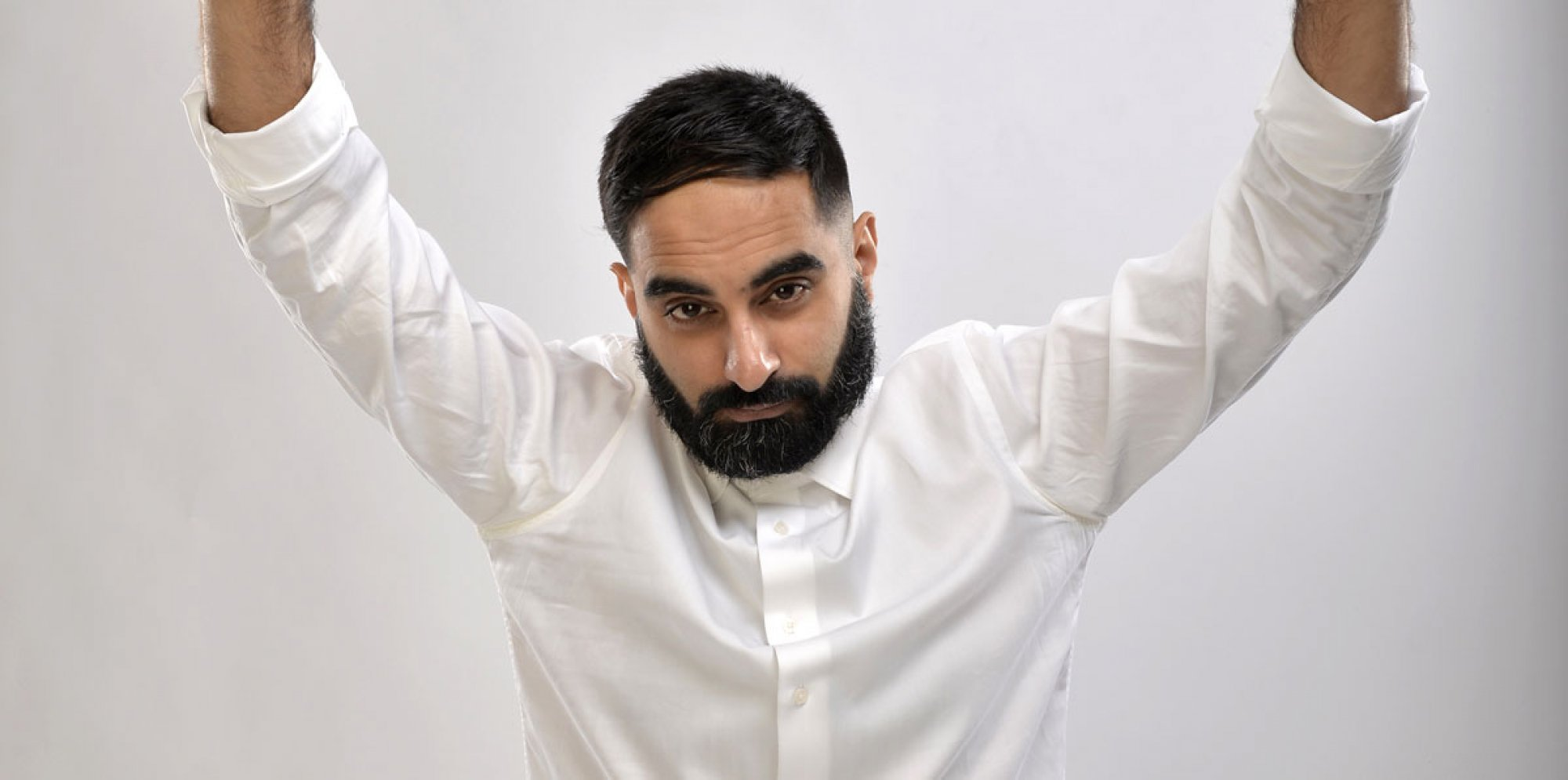 Tez Ilyas in a white shirt, holding his hands above his head