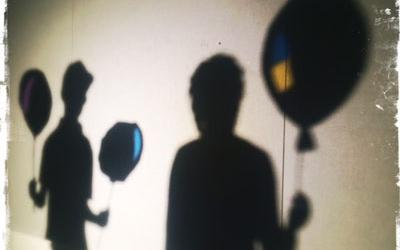 Shadow play of two boys holding balloons