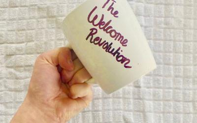 A raised fist holding a mug, writing on the mug reads The Welcome Revolution