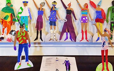 Cut outs of paper people all in different outfits and costumes, and a book of costume design