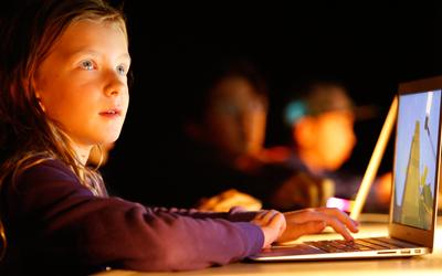 a young girl sits in front of a laptop. She is looking up and smiling. Her face is lit up by the laptop and an external light and glows yellow.