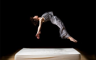 A dancer is hovering above a bed with an arched back as if they're about to land on the mattress