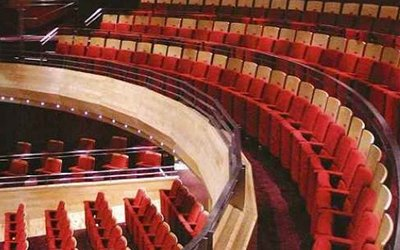 The interior of the Pentland Theatre, taken from the balcony. Rows of red seats curve around the right hand side of the image, and we are looking down on seats below. There are no people in the image.
