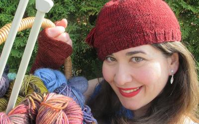 Stitch in Time Knitting Cabaret Melanie Gall lifting a basket filled with colourful wool