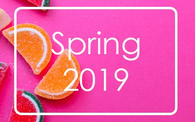 a pink background with multicoloured, orange slice-shaped jelly sweets and the words Spring 2019 Season