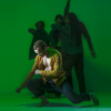 BalletBoyz: a man in a yellow open shirt and blue trousers, lunging above the floor, looking pensive. Three figures can be seen in the shadow behind him. The background is green.