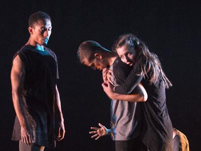 201 Dance: a group of performers hugging in diffuse stage lighting