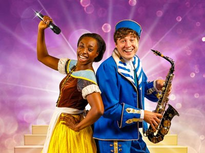A woman in a medieval maid dress and a man in a panto page costume. She's holding a mic, he's holding a saxophone, they're both smiling brightly.