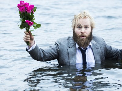 A man in a suit is chest deep in water. He is holding a bouquet of pink roses in one hand.