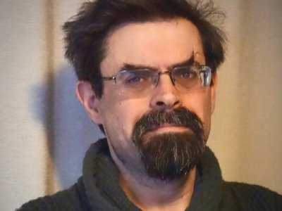 Adrian Tchaikovsky is pictured from the shoulders up. He is a white man with dark brown hair and a beard, he is wearing glasses.