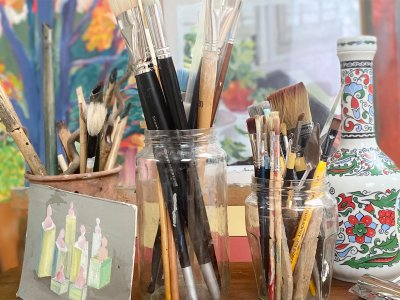 A table with three pots full of different paintbrushes, a floral vase and a small painting