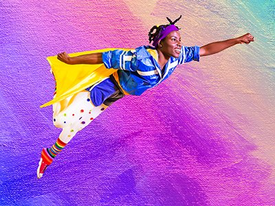 A young woman is in a superhero pose with one arm stretched out in front of her as if she's flying like superman. She is wearing a yellow cape, stripy legwarmers, spotty leggings and a blue top. She looks happy.