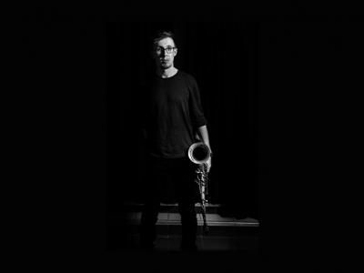 Black and white photo of saxaphonist Alex Hitchcock.