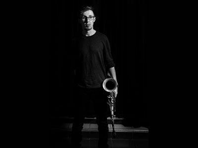 Black and white photo of saxaphonist Alex Hitchcock.