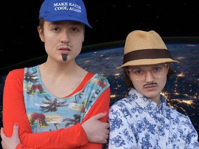 "Alice Boyd and Rosa Garland dressed as men with drawn-on sharpie beards, Rosa wearing a ""Make Earth Great Again"" hat"
