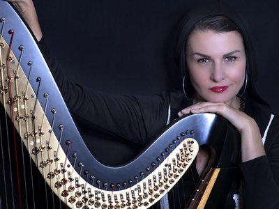 A woman is smirking at the camera. She is leaning on a harp.