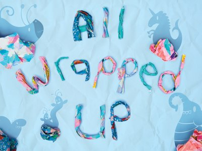 The words 'All Wrapped Up' made from twisted gift paper. Around them, bunches of gift paper throw shadows that look like fantasy animals with round eyes and antlers.