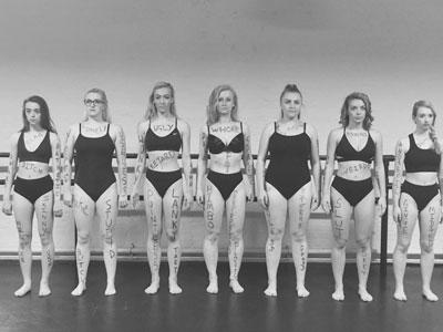 A row of young women in swimwear with derogatory words scribbled on their limbs.
