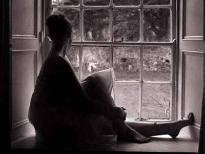 a black and white image of a woman sitting on a window sill and looking out of a tiled window