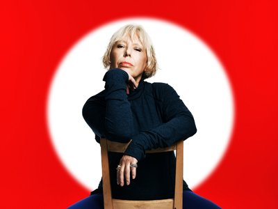 Barb Jungr sitting on a backward chair, her chin resting on her hand. Her head is lit by a white spotlight against an otherwise stark red background