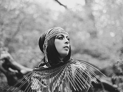 A black and white photo of Bella Scar, she has bold glittering eye make up and wears a beaded headdress and a neckpiece which has long spikes coming from it