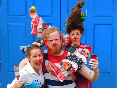 Three clowns dressed in bright colours pulling faces