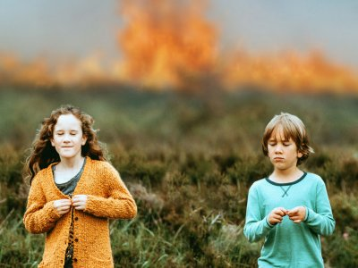 Two children stand apart against the background of a grassy field