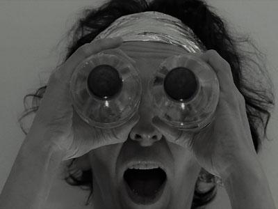 an astonished face of a person, holding waterbottles in front of their eyes