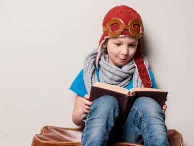 a boy wearing a hat and pretend-pilot goggles, sits against a wall and reads a book with obvious delight