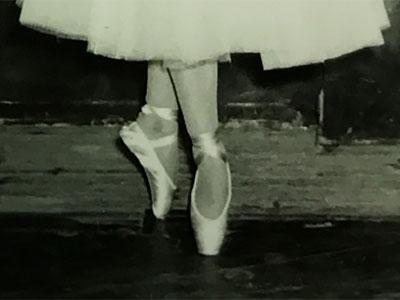 old black-and-white photograph of a ballerina's feet in ballet shoes on pointe