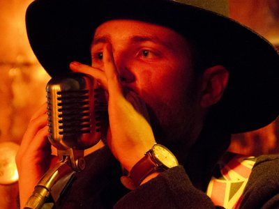 A man in a black wide brimmed hat is singing into a microphone. Theres a guitar in the background.