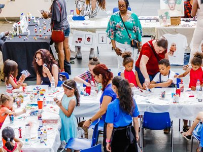 artsdepot CEP: children and parents sit around an L-shaped table making oild paintings. Stewards in blue t-shirts watch or have conversations with them. In the backgrounds, people gather at arts market stalls