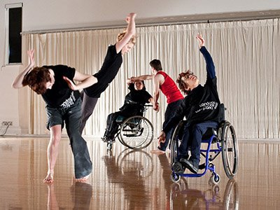 Five dancers in a rehearsal studio, all are wearing black candoco dance company tshirts and are making dynamic movements. Two dancers are wheelchair users.