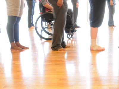 Photo of people lined up - legs, feet and the lower half of wheelchairs can only be seen.