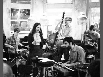 A black and white photo showing a band playing, with a singer, guitarist, keyboardist, drummer and cello player.
