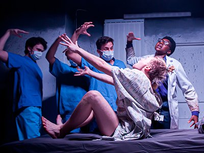 Apicture of Chalk Line Theatre on stage. A performer wearing a hospital gown is surrounded by others dressed as doctors.