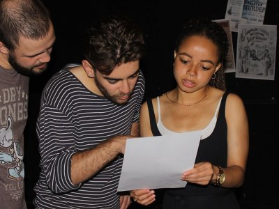 A woman wearing a dark vest top is holding a piece of paper in both hands, a man points at something on the page while another man looks at it over his shoulder.