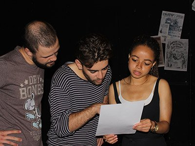 A female performer holds a piece of paper, a man is pointing at something on the page and another man looks over his shoulder.