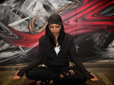 A woman wearing a hooded windcheater sitting in lotus pose with graffiti wall behind her.