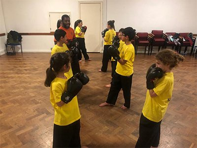 Pairs of children face each other wearing yellow t-shirts and black boxing gloves, the teacher stands by offering guidance