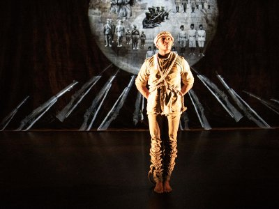 A man stands on the stage, he wears beige clothing with ropes tied around him, in the background there's a projection with images of soldiers, a soldiers uniform and a gramophone