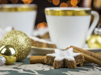 Two gold rimmed coffee cups are blurry in the background, in the foregrount are gold coloured baubles, iced biscuits and cinnamon sticks