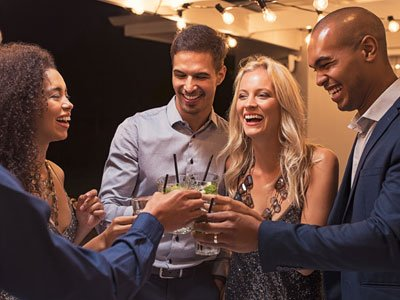 A group of five men and women toast with their drinks, all are smartly dressed and smiling