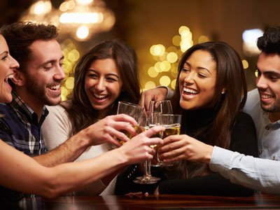 A group of five men and women toast with glasses of wine and beer, all are smiling and there are twinkly golden lights in the background