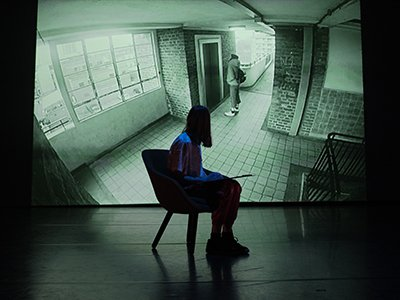 A person sits on a chair in front of a projection of someone waiting by the lift in a flat block