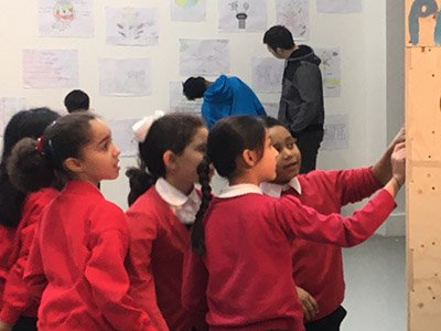 A group of primary school aged children looking at something attached to a wooden structure. In the background, older young people look at drawings attached to a white gallery wall.
